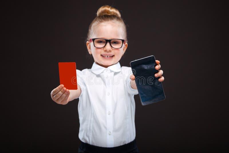 白色衬衣的可爱的逗人喜爱的女孩和黑长裤举行红牌和展示电话 库存图片