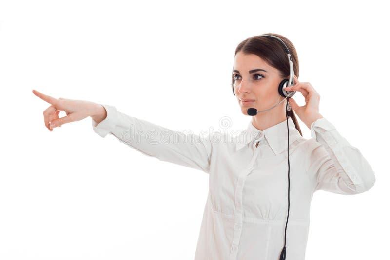 白色衬衣的女孩站立在耳机和提供援助往 库存图片