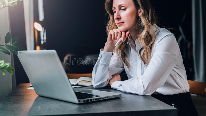 白色衬衣的女实业家在办公室坐在计算机前面的桌上和沉思地看膝上型计算机屏幕  图库摄影