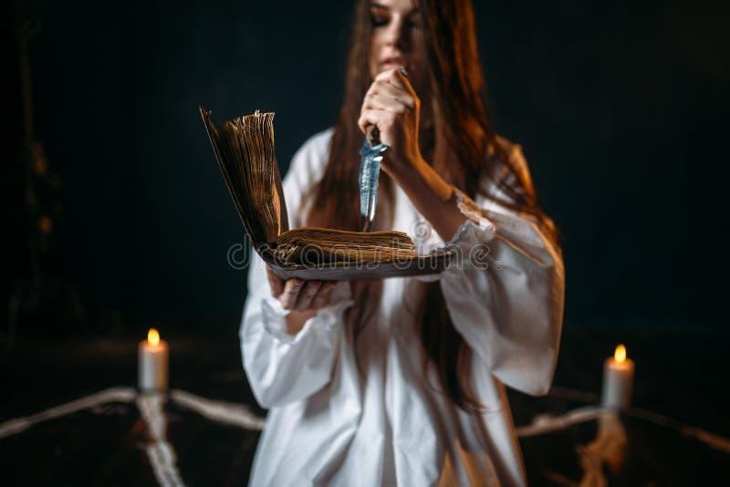 白色衬衣的巫婆拿着刀子并且读咒语 库存图片
