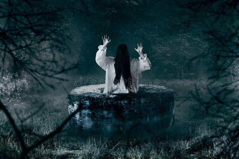 白色衬衣的巫婆离开一口被放弃的井 免版税库存照片
