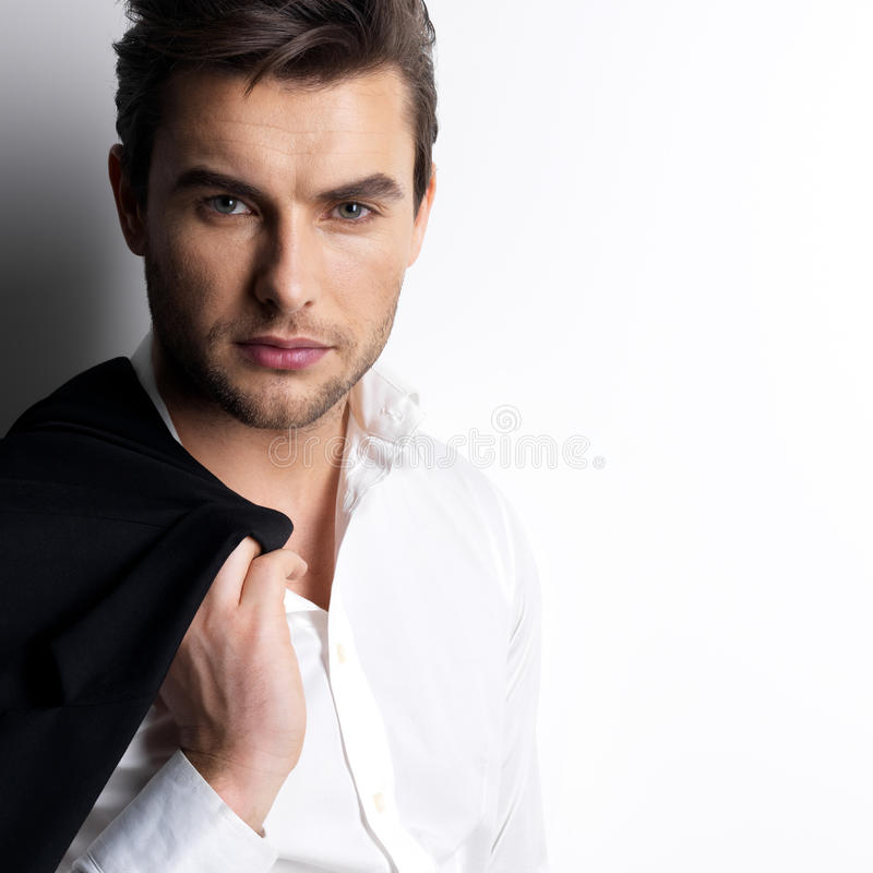 白色衬衣的时尚年轻人拿着黑夹克 免版税库存照片