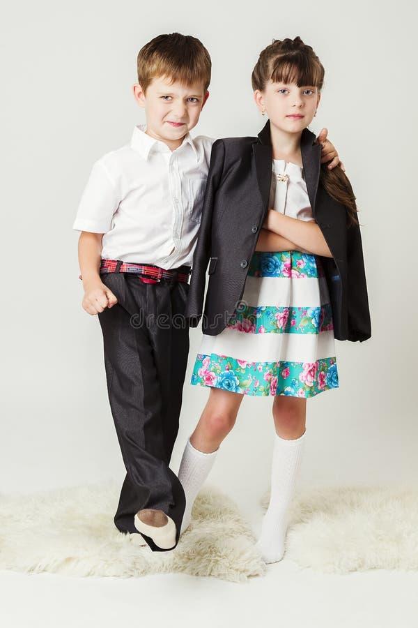 白色衬衣的男孩由肩膀拥抱一个女孩 库存照片