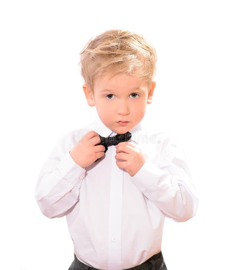 白色衬衣的白肤金发的男孩有黑蝶形领结的 库存照片