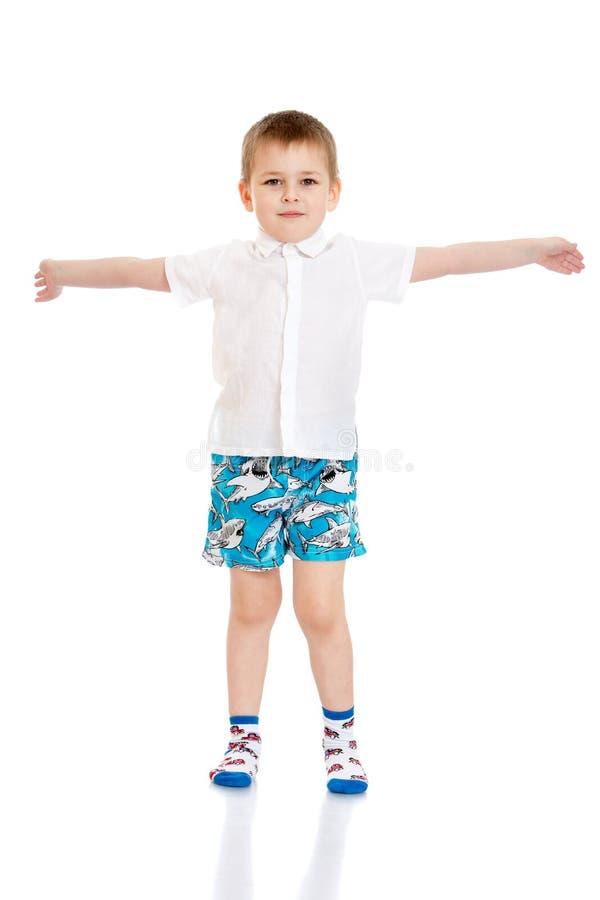 白色衬衣的,短裤美丽的小男孩和 免版税库存照片