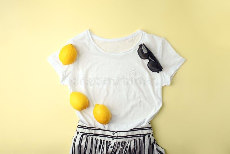 白色衬衫、太阳镜和柠檬在黄色背景 妇女的时髦的春天夏天成套装备 时髦衣裳   库存图片