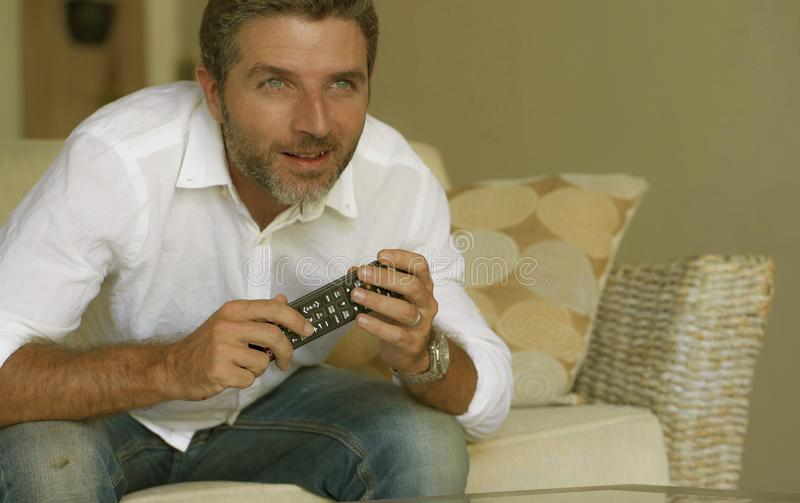 白色衬衫和牛仔裤的观看在客厅的年轻激动和可爱的人家庭生活方式画象电视开会 免版税图库摄影