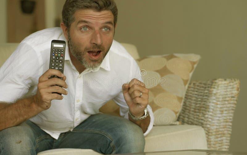 白色衬衫和牛仔裤的观看在客厅的年轻激动和可爱的人家庭生活方式画象电视开会 库存照片