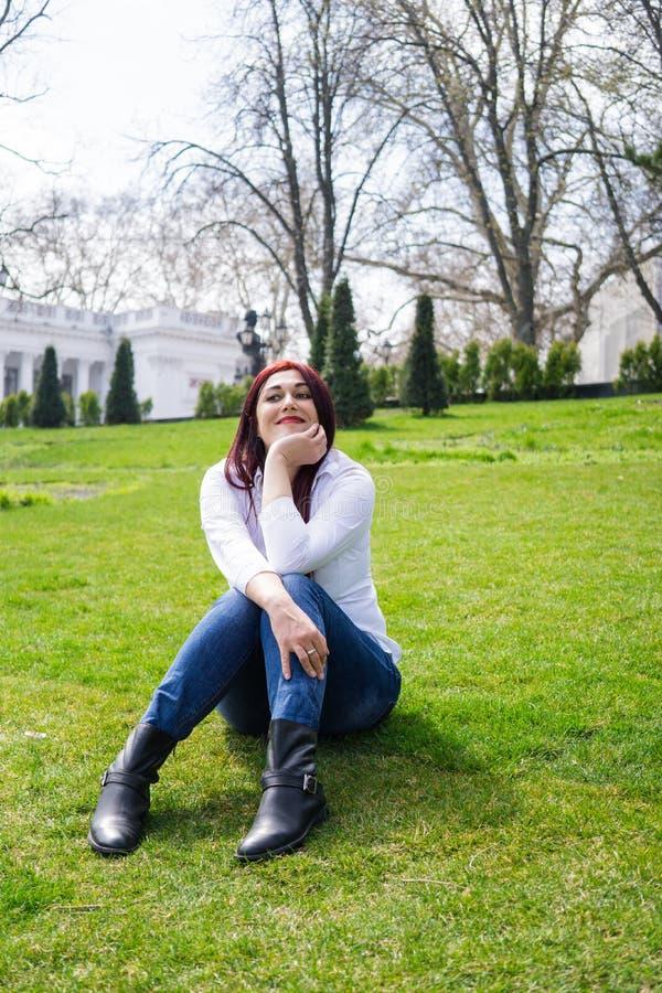 白色衬衫和蓝色牛仔裤的年轻女人坐绿草 库存图片