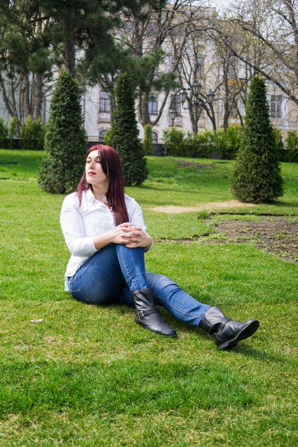 白色衬衫和蓝色牛仔裤的年轻女人坐绿草 图库摄影