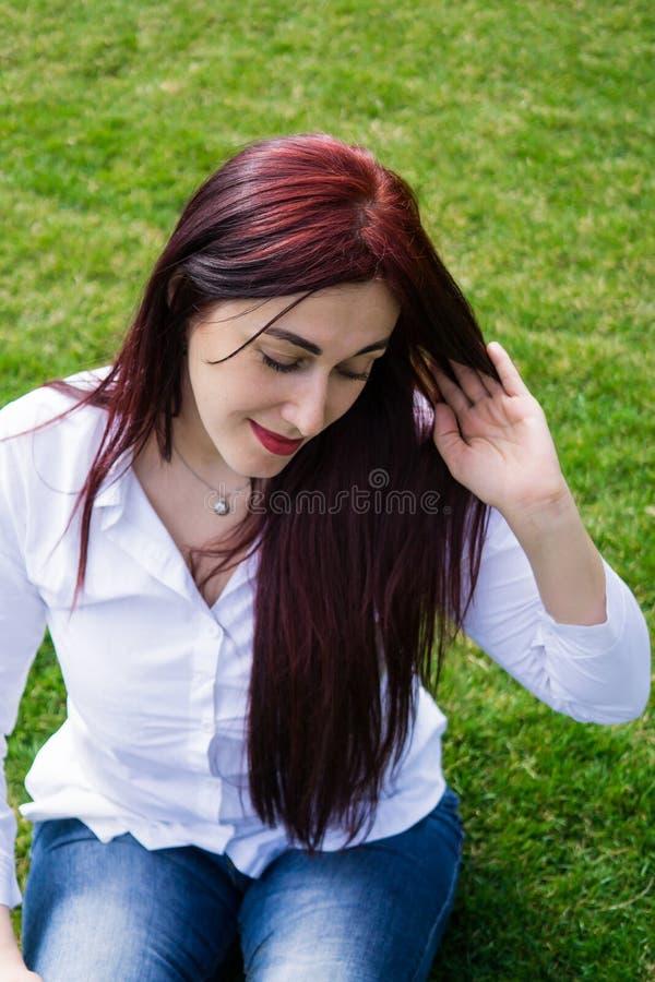白色衬衫和蓝色牛仔裤的年轻女人坐绿草 免版税库存图片