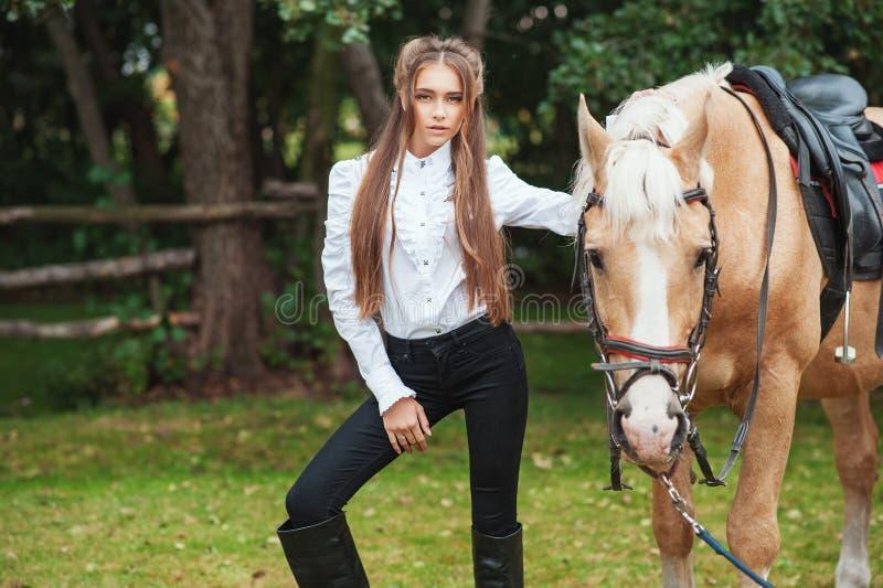 白色衬衫和黑色裤子的画象美丽的少女有在森林时兴的高雅woma的秀丽长发下匹马的 免版税库存图片