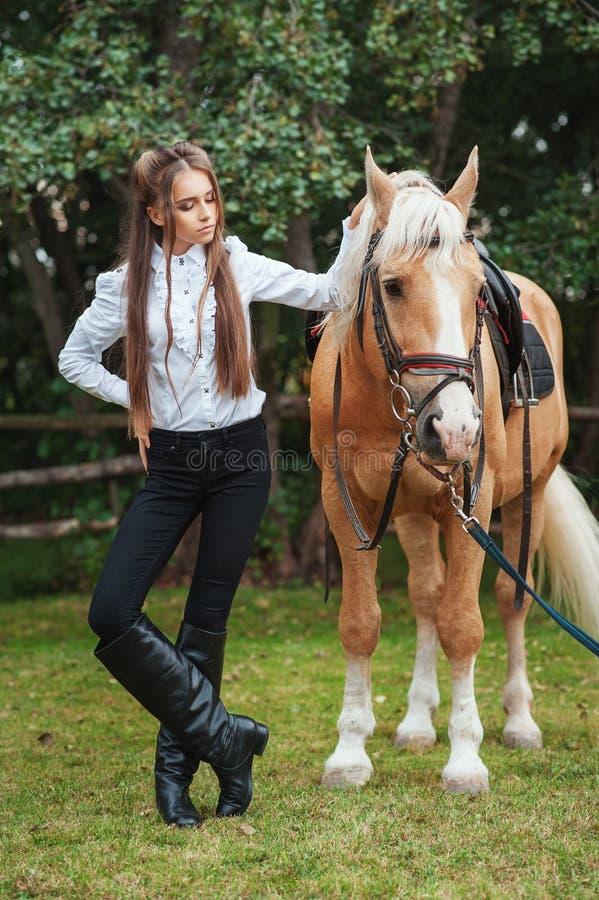 白色衬衫和黑色裤子的画象美丽的少女有在森林时兴的高雅woma的秀丽长发下匹马的 免版税库存照片