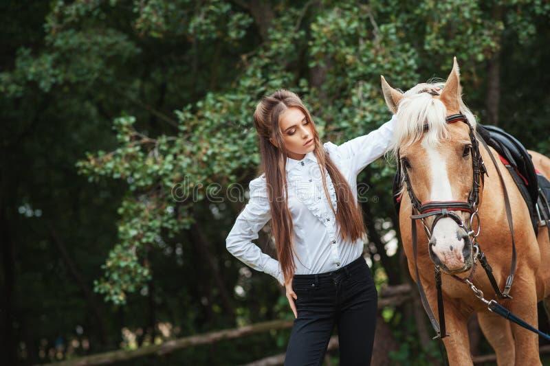 白色衬衫和黑色裤子的画象美丽的少女有在森林时兴的高雅woma的秀丽长发下匹马的 图库摄影