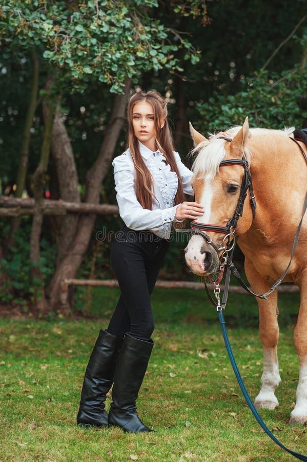 白色衬衫和黑色裤子的画象美丽的少女有在森林时兴的高雅woma的秀丽长发下匹马的 库存照片