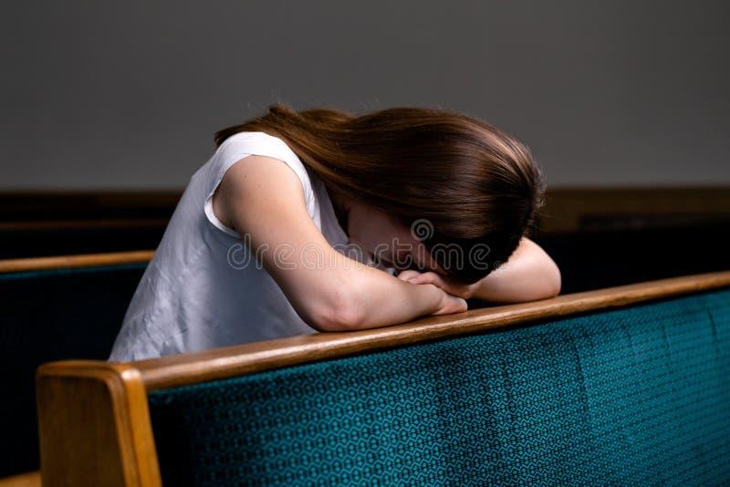 白色衬衫的一个哀伤的基督徒女孩是坐和祈祷与谦逊的心脏在教会里 库存照片
