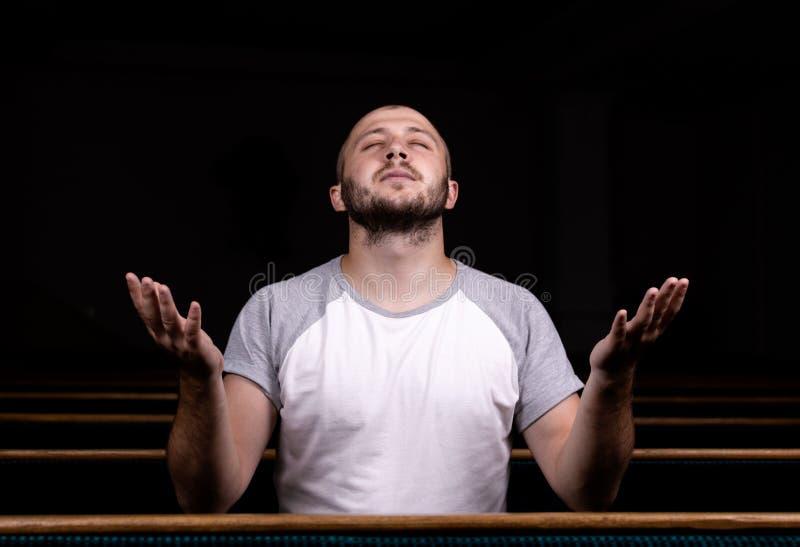 白色衬衫的一个基督徒人坐用他的手并且祈祷与谦逊的心脏在教会里 免版税图库摄影
