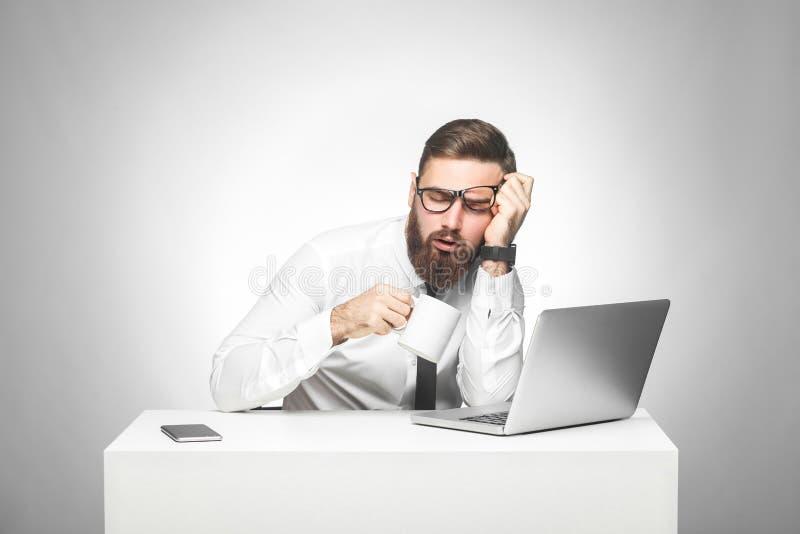 白色衬衫的不负责任疲乏的年轻经理和半正式礼服在办公室在工作,饮料a坐并且设法不睡觉 免版税库存照片