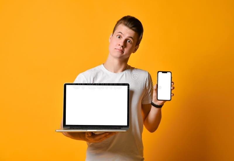 白色衬衫的人,拿着手提电脑和流动智能手机,身分在框架显示电话和计算机屏幕  库存照片