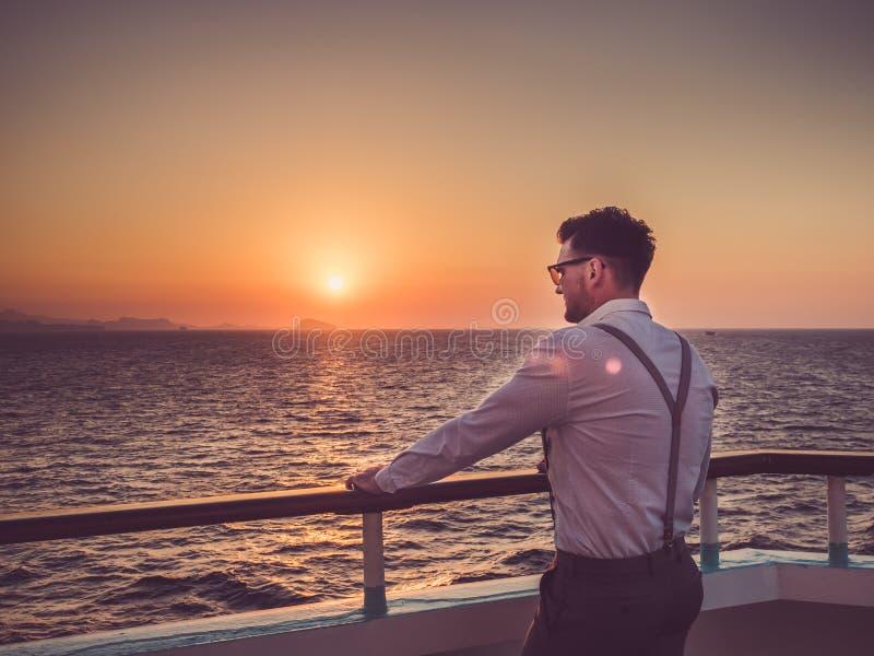 白色衬衫的可爱的人在甲板 免版税库存图片