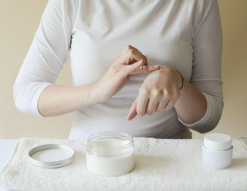 白色衬衫的女孩整洁地显示她并且养育了在奶油色毛巾安置的手 r 润肤霜的应用 库存照片