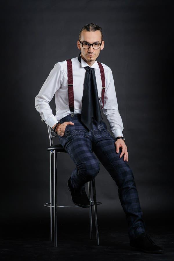 白色衬衫的年轻帅哥有领带的坐椅子 库存图片