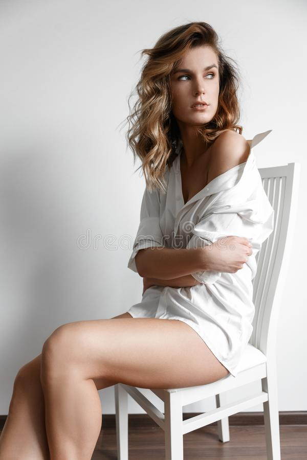 白色衬衫的性感女孩在一把白色椅子 库存照片
