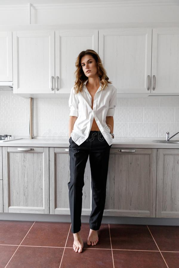 白色衬衫的深色的女孩在厨房里 免版税库存图片