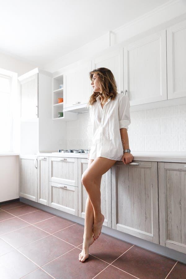 白色衬衫的深色的女孩在厨房里 免版税图库摄影
