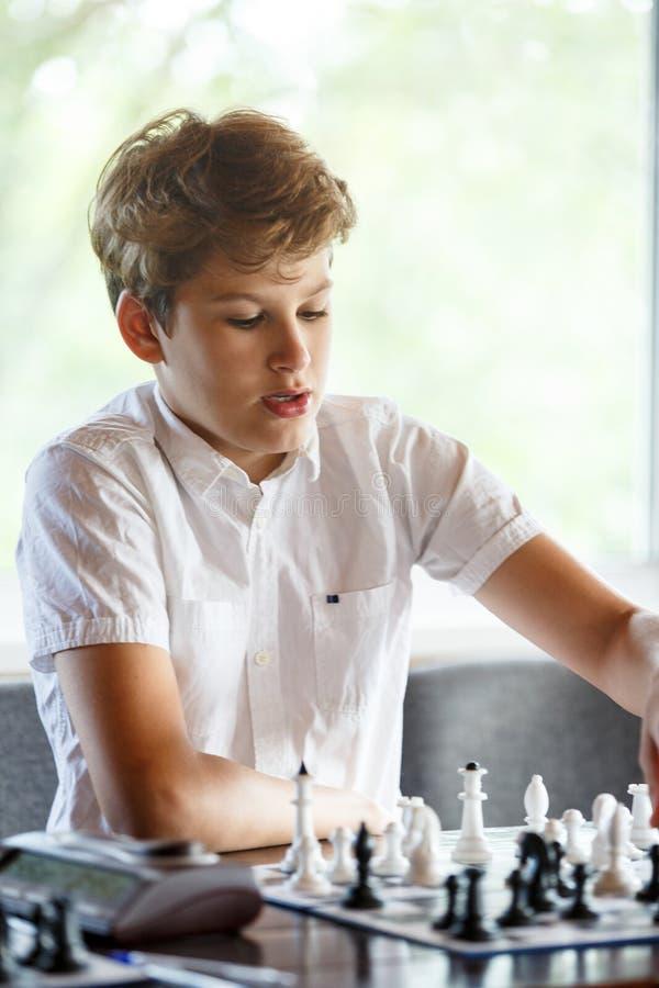白色衬衫的逗人喜爱,聪明,年轻男孩在教室下在棋枰的棋 教育,爱好,训练 免版税库存图片