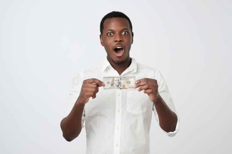 白色衬衫的非洲人在他的看照相机的手上拿着一百美元 图库摄影