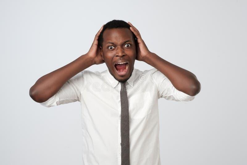白色衬衫的非裔美国人的人和领带尖叫在恐慌,震惊听见坏消息 免版税库存图片