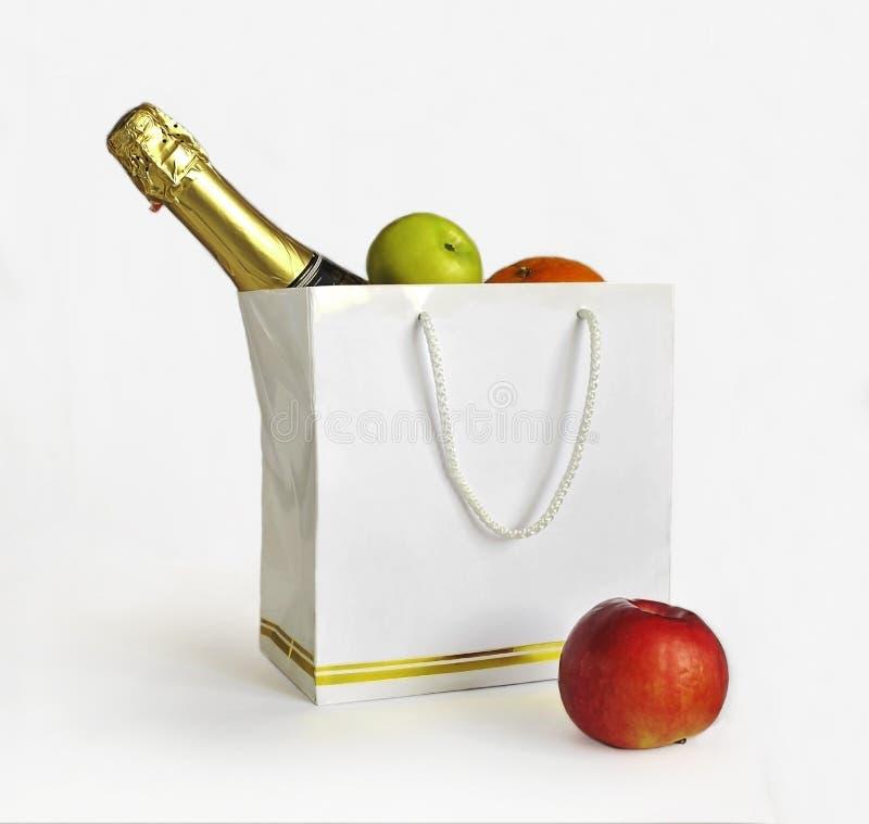 白色袋子用里面果子和香槟 免版税库存图片
