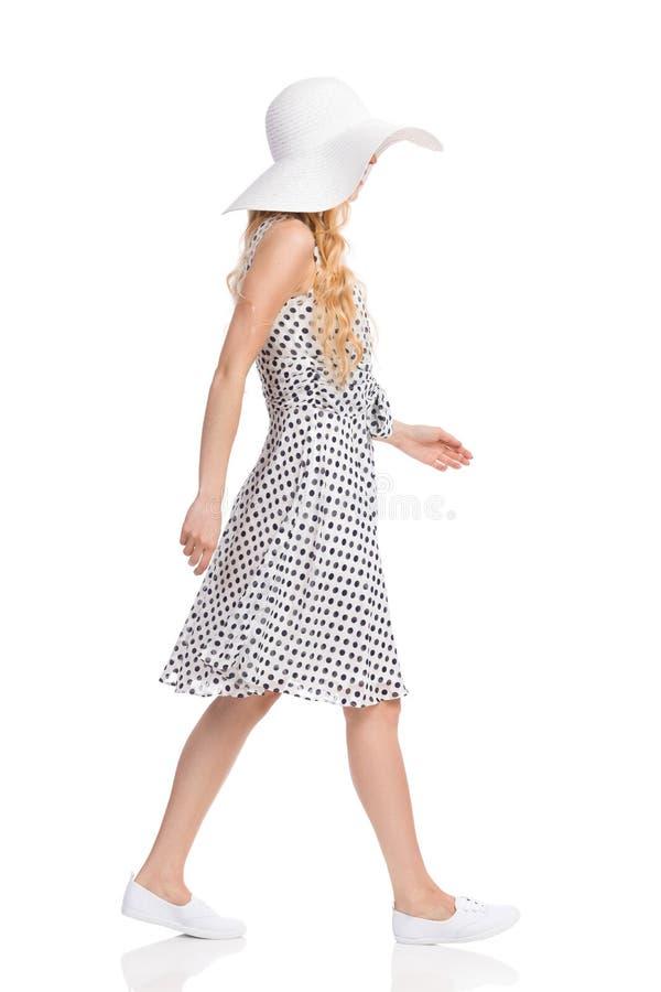 白色被加点的礼服、太阳帽子和运动鞋的走的妇女 库存照片