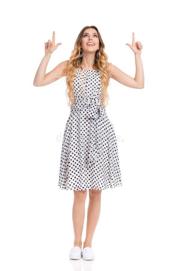 白色被加点的礼服的好奇少妇查寻和指向 免版税库存照片