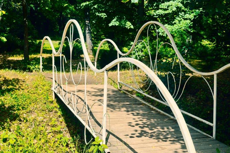 白色被打造的桥梁在庭院里 免版税库存照片