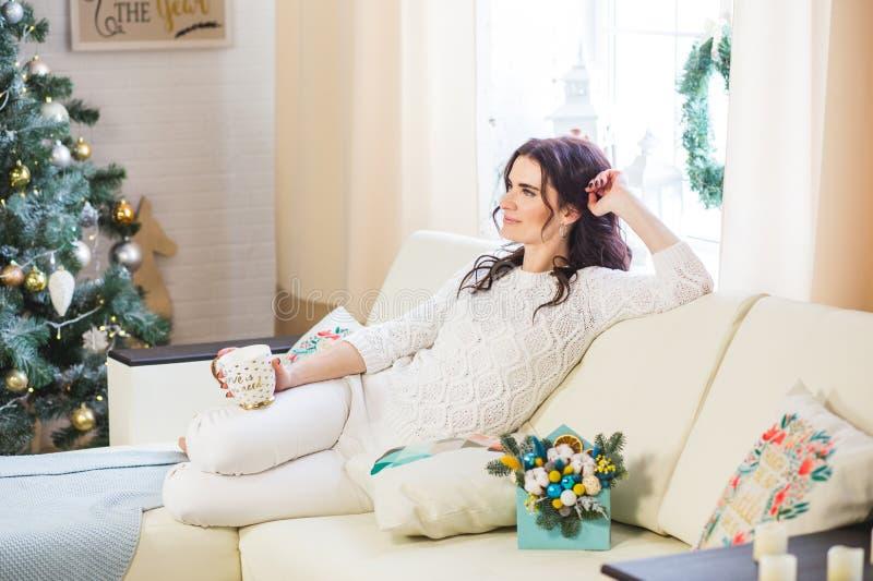 白色被编织的在家佩带的愉快的年轻女人与咖啡或茶 库存照片