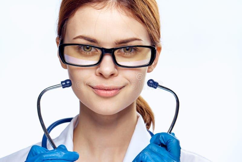 白色被隔绝的背景的年轻美丽的妇女与玻璃拿着一个听诊器,画象,医学医生, 库存图片