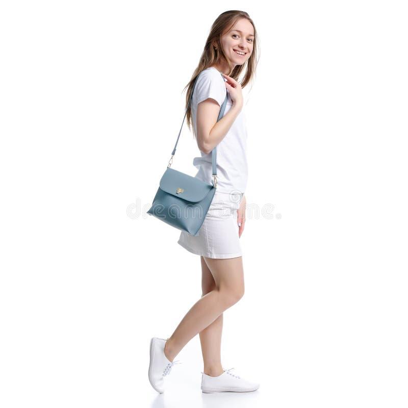 白色裙子和T恤杉的妇女有看起来的袋子的走去 库存图片