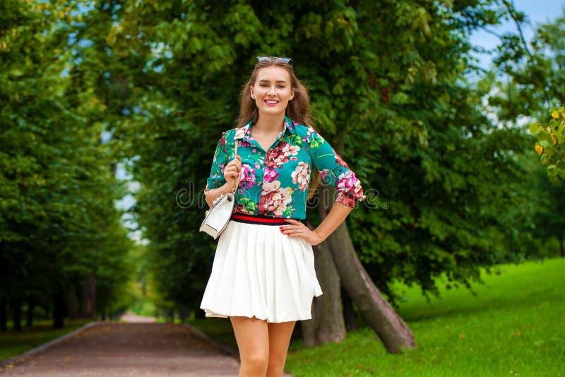 白色裙子的年轻深色的妇女 免版税库存图片