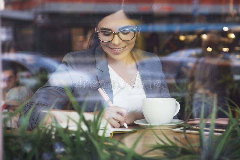白色裙子的美丽的深色的女商人和从咖啡馆的灰色衣服夹克工作 她戴眼镜并且喝杯子  库存照片