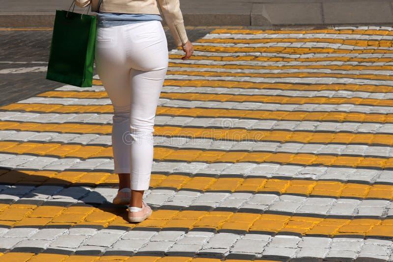 白色裤子的妇女走在行人交叉路,背面图的 免版税库存照片