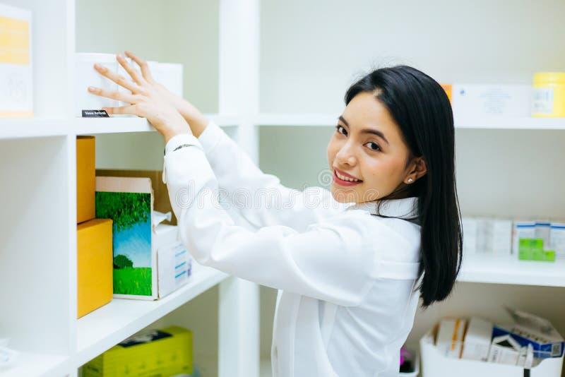 白色褂子的亚裔药剂师医生检查医疗健康股票产品和工作在药房的在商店 图库摄影