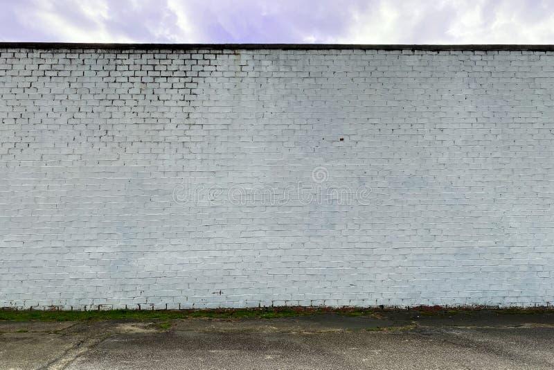 白色褪色的石砖厂仓库墙巷 库存图片