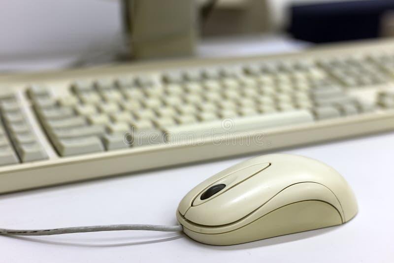白色计算机老鼠特写镜头在被弄脏的个人计算机键盘背景的 现代技术、信息和通信概念 免版税库存照片