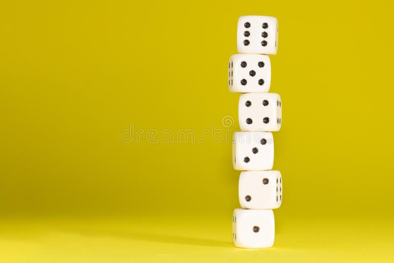 白色赌博在桃红色背景切成小方块 胜利机会,幸运 平的位置,文本的地方 顶视图 特写镜头 概念赌博 免版税图库摄影