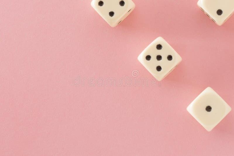 白色赌博在桃红色背景切成小方块 胜利机会,幸运 平的位置,文本的地方 顶视图 特写镜头 概念赌博 库存照片