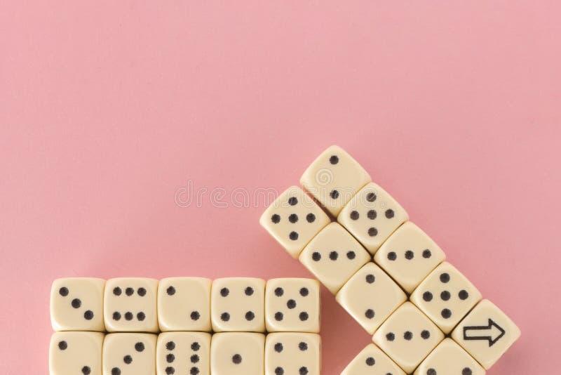 白色赌博在桃红色背景切成小方块 胜利机会,幸运 指针 平的位置,文本的地方 顶视图 特写镜头 概念 免版税库存图片