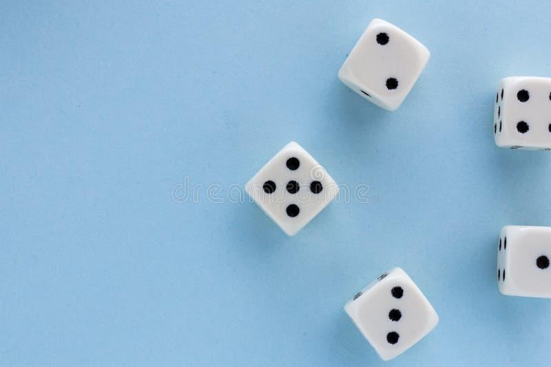 白色赌博在浅兰的背景切成小方块 胜利机会,幸运 平的位置,文本的地方 顶视图 特写镜头 概念赌博 免版税库存图片