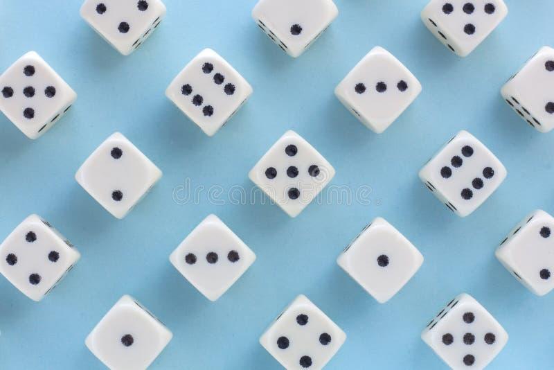 白色赌博在浅兰的背景切成小方块 胜利机会,幸运 平的位置,文本的地方 顶视图 特写镜头 概念赌博 图库摄影